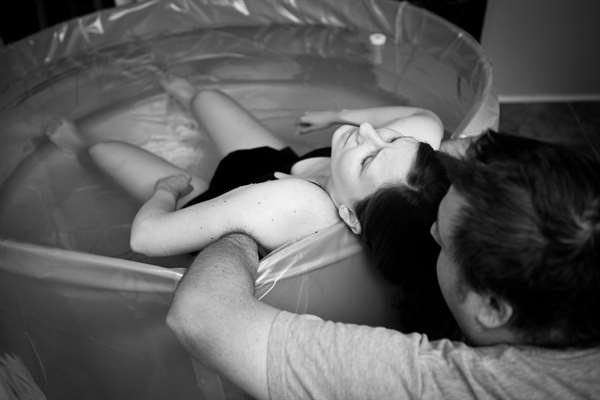 Hình ảnh đen trắng của một người chồng yêu thương hỗ trợ và huấn luyện người vợ của mình trong một ca sinh nở căng thẳng tại nhà.