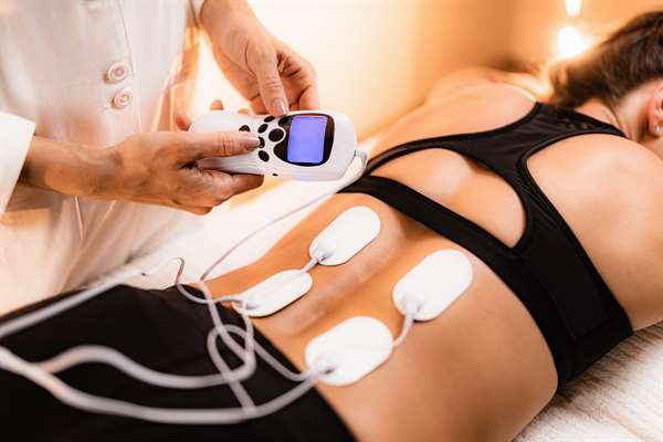 Vật lý trị liệu Lưng dưới với miếng đệm điện cực TENS, Kích thích dây thần kinh điện qua da. Điện cực vào lưng dưới của bệnh nhân